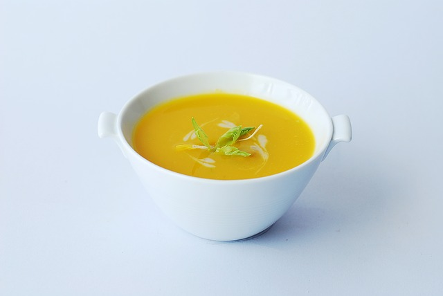 yellow pureed soup in white bowl on whitish gray background