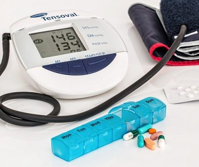 Blood pressure meter and blue pill box with pills spilling out