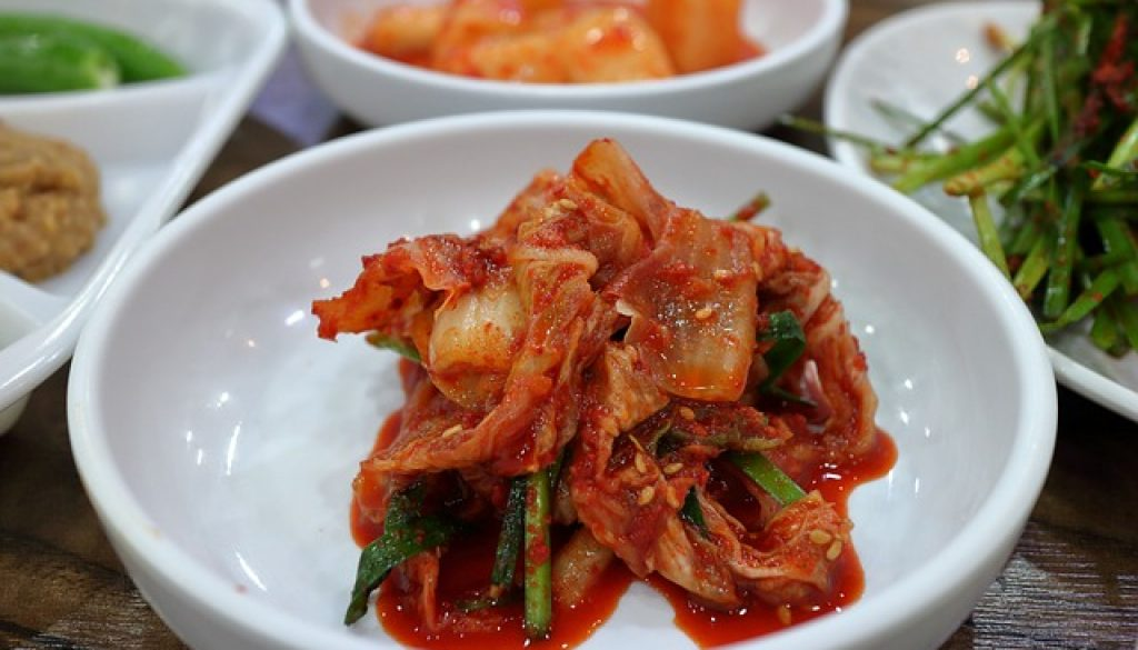 Bright red kimchi in a white bowl