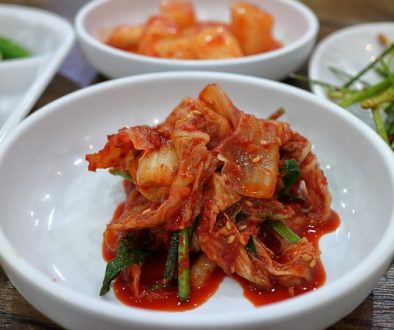 Bright red kimchi in a white bowl