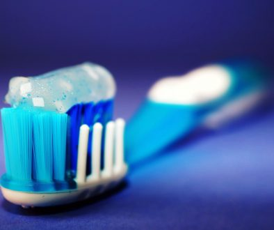 Blue green and white toothbrush with toothpaste on it against a dark purple background