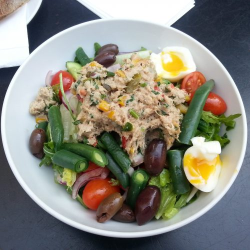 Salmon salad on top of a green salad of hard boiled eggs tomatoes lettuce green beans and olives