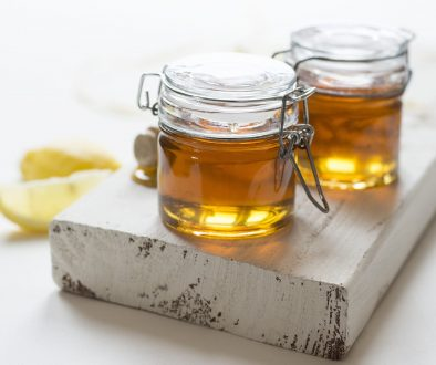 two jars of honey sitting on top of a whitewashed board against a white background with a lemon slice nearby