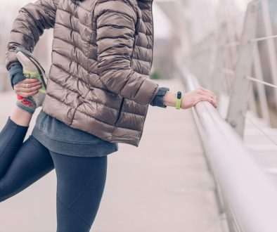 woman holding onto a rail and stretching her leg getting ready to go for a run
