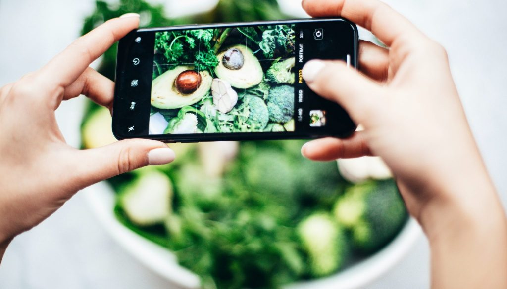 Two hands holding an iPhone snapping a picture of an avocado that's cut open