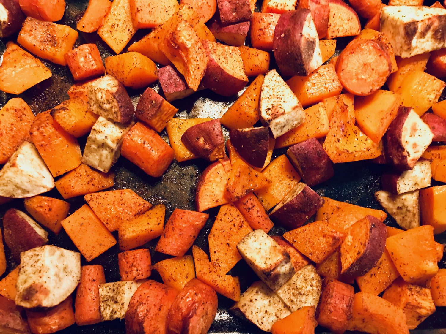 roasted sweet potatoes carrots and butternut squash in a glass baking dish
