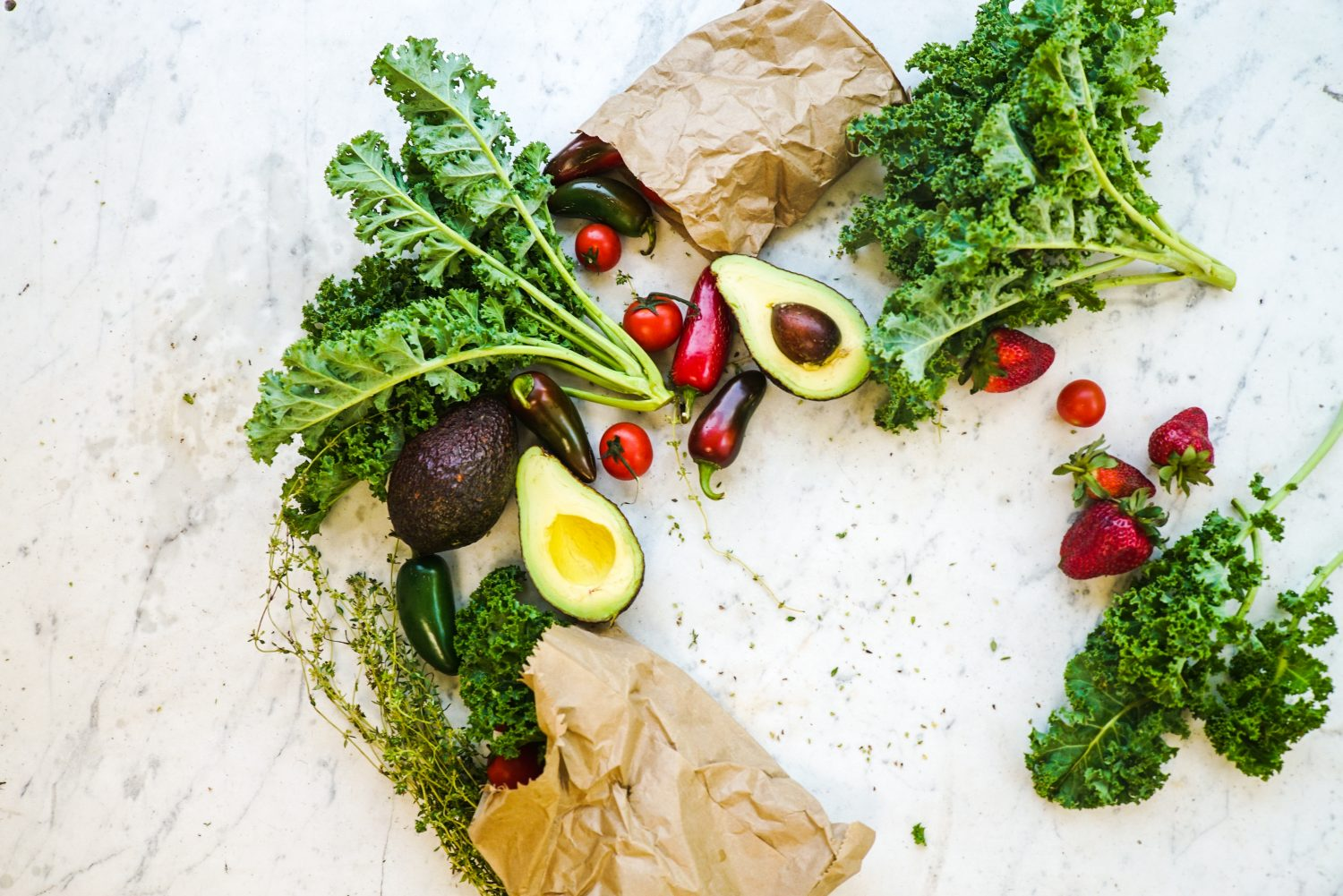 Two bags of healthy groceries - kale, avocados, strawberries - spilling onto a gray marble counter