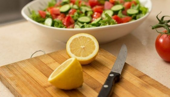 Picture of cutting board with knife and sliced lemon on it - salad in the background