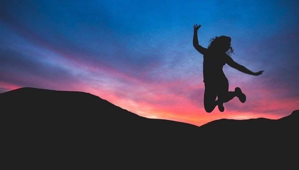 Silhouette of woman jumping in sunset