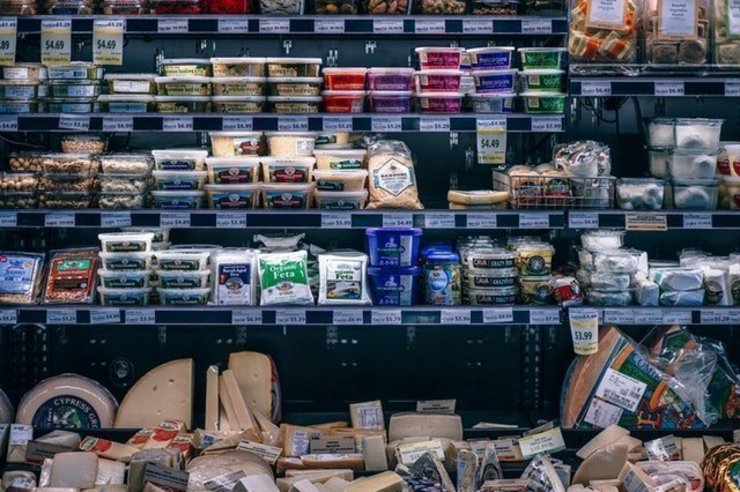 Assorted cheeses and meats on refrigerated shelves in the grocery store