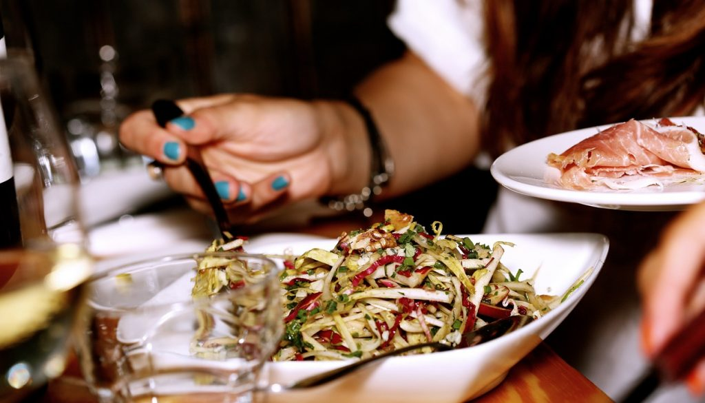 Picture of a woman eating salad at a restaurant