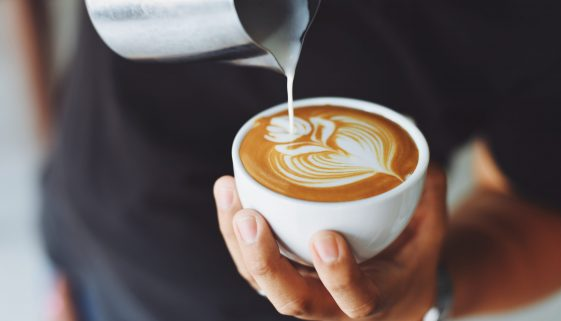 Picture of person swirling heavy cream into cup of coffee