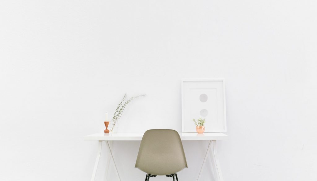 Picture of uncluttered desk in front of white wall