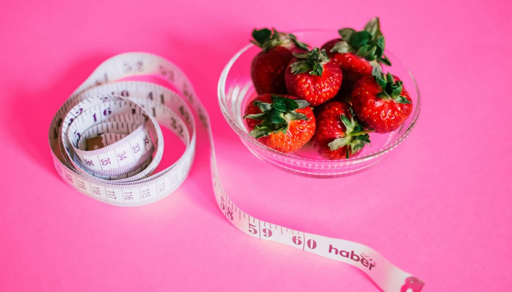 bowl of strawberries and paper tape measure against a pink background