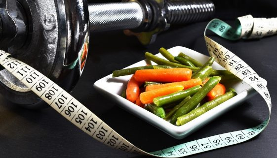 Picture of barbell, measuring tape, and a plate of vegetables