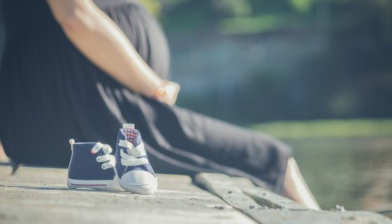 Picture of pregnant woman sitting next to baby shoes