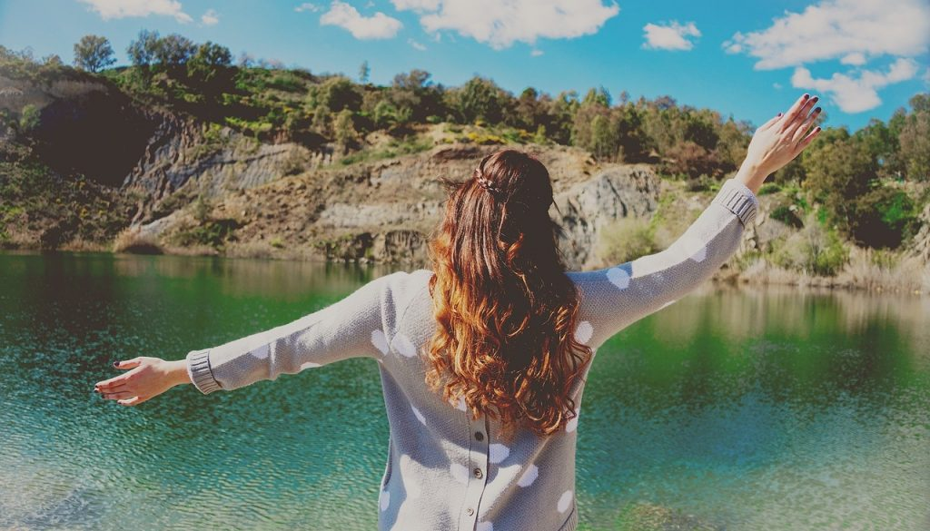 Picture of woman with arms up in front of water and mountains