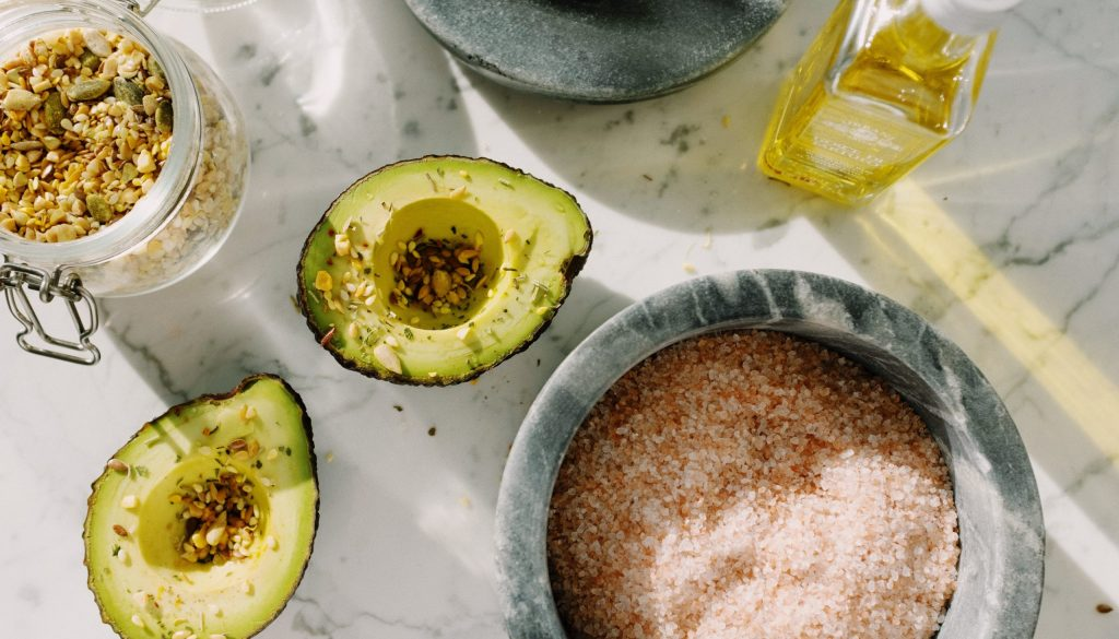 Picture of pink salt, an avocado, and olive oil