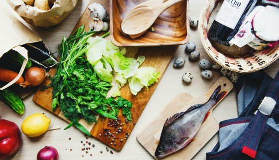picture of seasonings, greens, and fish, ready to be prepared