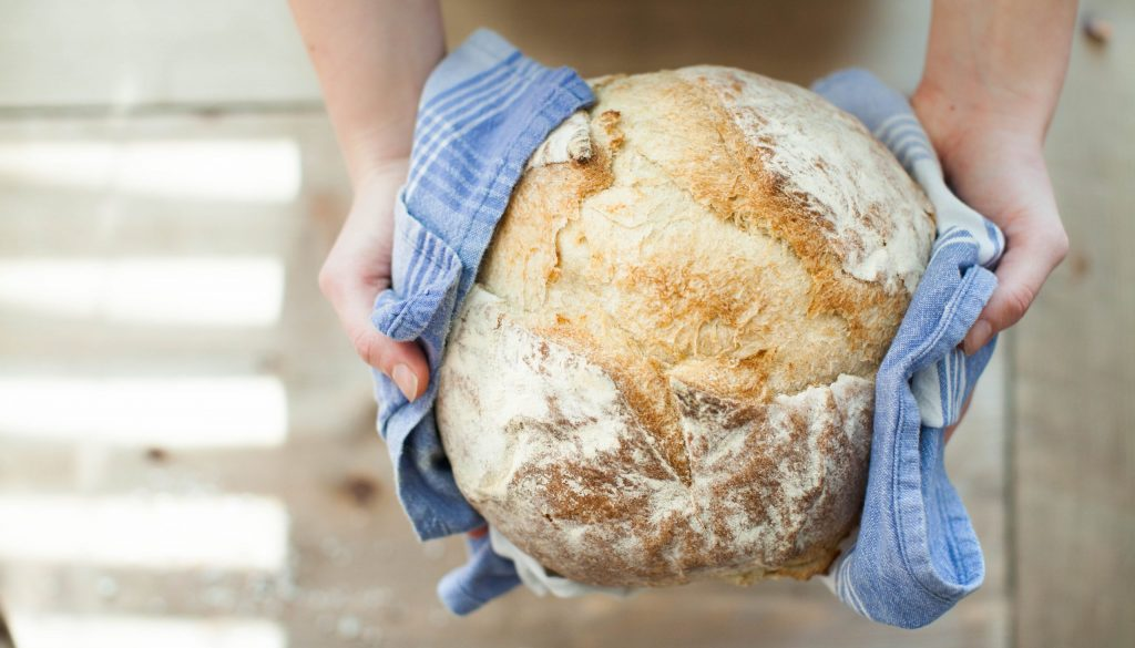 Person holding a loaf of fresh-baked sourdough bread