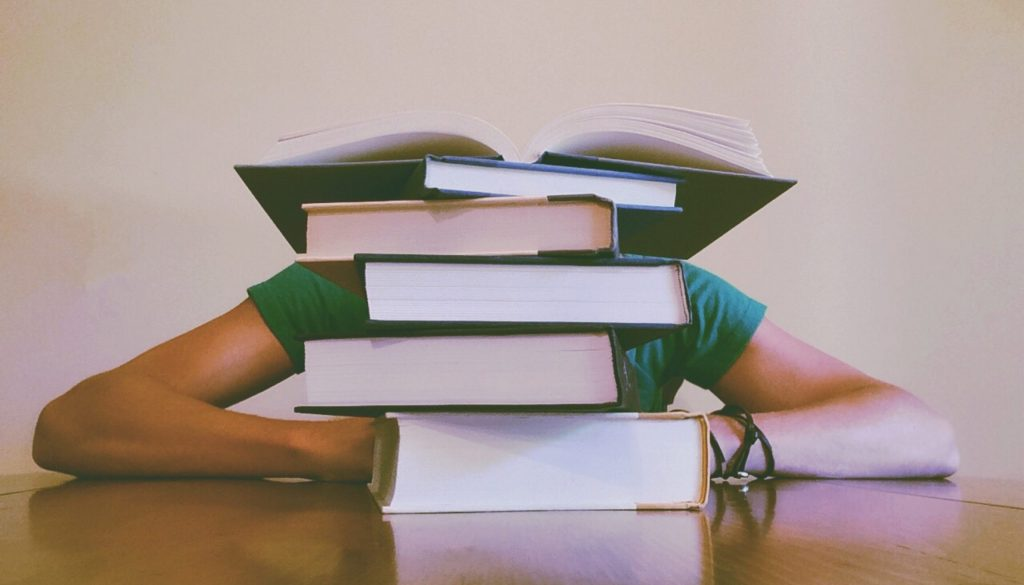picture of person feeling stressed behind a stack of books
