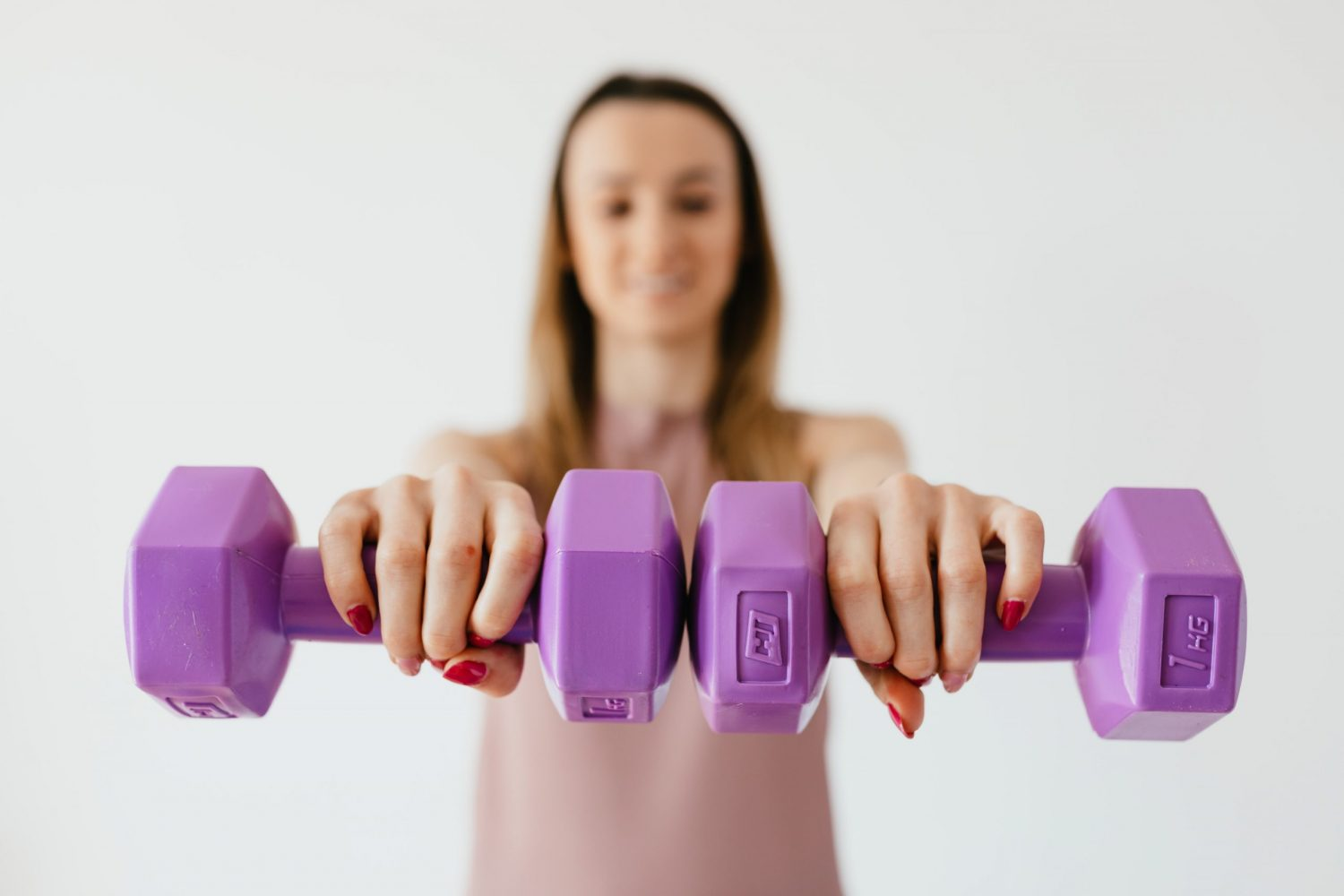 Woman holding two pink dumbbells out in front of her